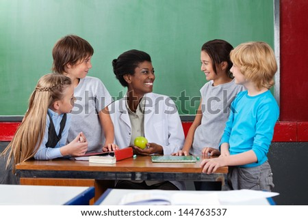 Schoolchildren looking young African American teacher sitting at desk in classroom - stock photo