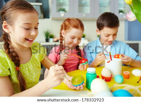 Schoolchildren painting eggs for Easter - stock photo