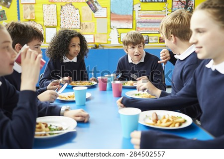 Schoolchildren Sitting At Table Eating Cooked Lunch - stock photo
