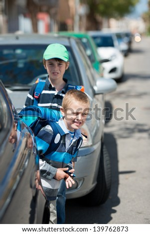 Schoolchildren waiting between the parked car outdoors - stock photo