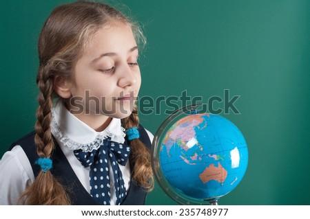 schoolgirl and globe - stock photo