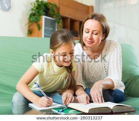 schoolgirl and woman together doing homework in home - stock photo