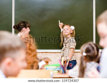 schoolgirl answers questions of teachers near a school board - stock photo