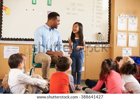 Schoolgirl at front of elementary class talking with teacher - stock photo
