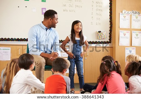 Schoolgirl at front of elementary class with teacher - stock photo