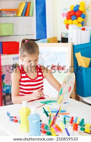 Schoolgirl draws drawing - stock photo