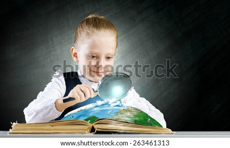 Schoolgirl examining opened book with magnifying glass. Elements of this image are furnished by NASA - stock photo