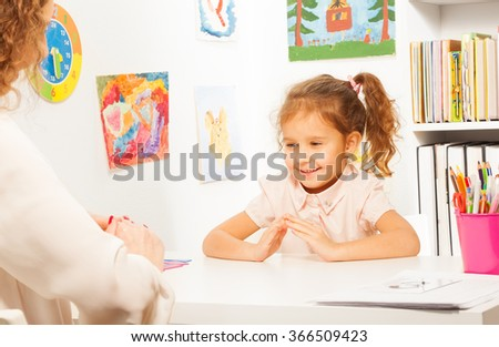 Schoolgirl exercises putting fingers like teacher - stock photo