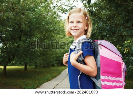 Schoolgirl goes to school with school bag. - stock photo