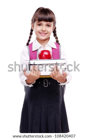 schoolgirl in uniform standing on white background and holding books and apple - stock photo