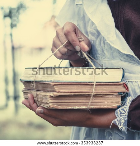 Schoolgirl keeps in hand books tied with cord. - stock photo
