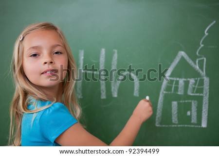 Schoolgirl learning the alphabet on a blackboard - stock photo