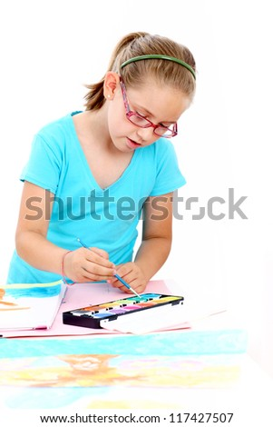 Schoolgirl painting with watercolor on white background - stock photo