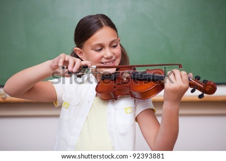 Schoolgirl playing the violin in a classroom - stock photo