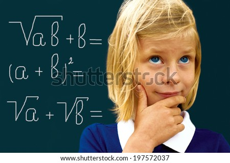 Schoolgirl ponders solving a mathematical problem standing at the blackboard  - stock photo