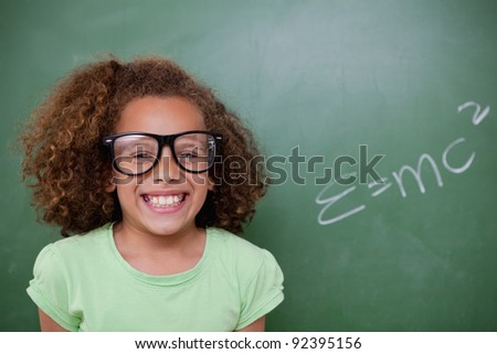 Schoolgirl posing with the the mass-energy equivalence formula on a blackboard - stock photo