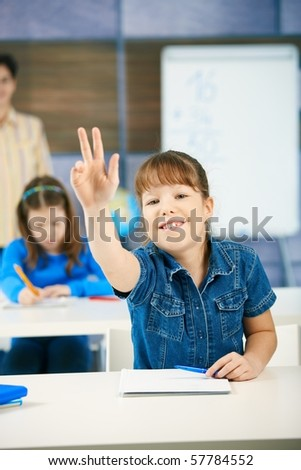 Schoolgirl raising hand to answer question smiling, other girl and teacher in background of class.? - stock photo