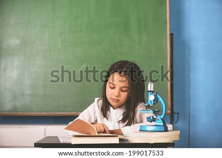 Schoolgirl sitting and learning at school desk - stock photo