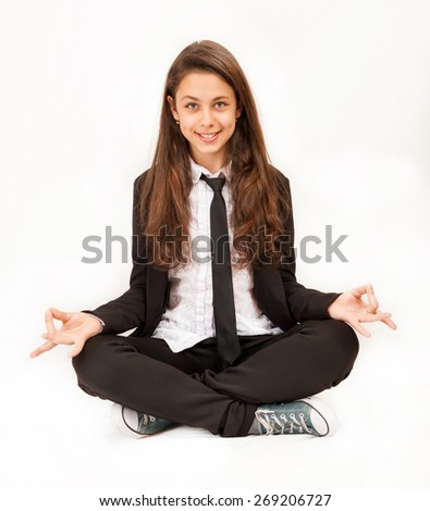 Schoolgirl sitting in the lotus position - stock photo