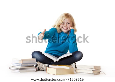 Schoolgirl sitting with books on floor and showing thumb up. Isolated on white background. - stock photo