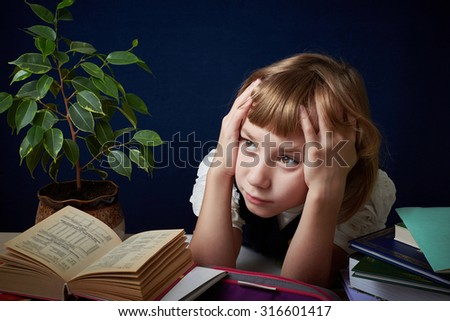 Schoolgirl tired of doing difficult homework. She wants to play with her friends in the yard, but you need to do your homework. - stock photo