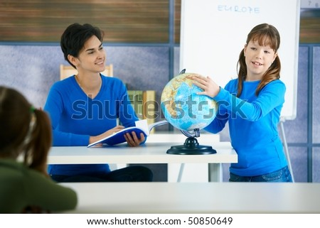 Schoolgirl touching globe in class, teacher smiling holding workbook. - stock photo