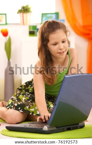 Schoolgirl using laptop at home, sitting on floor, smiling.? - stock photo