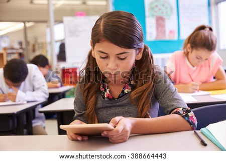 Schoolgirl using tablet computer in elementary school class - stock photo
