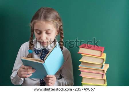 schoolgirl with a book on the background of the school board - stock photo