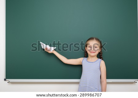 Schoolgirl with paper toy ship near school board - stock photo