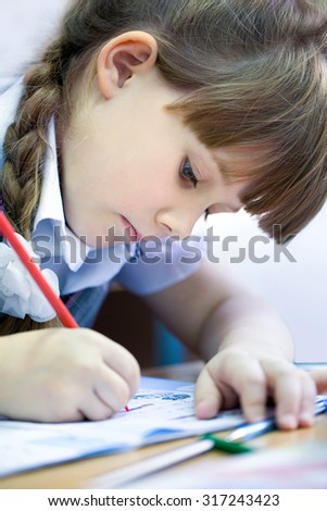 schoolgirl with pen writing in a notebook in classroom - stock photo