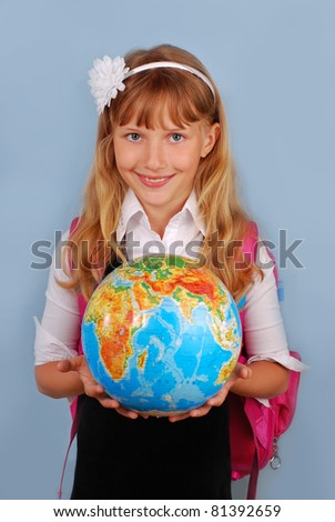 schoolgirl with pink backpack holding globe  against blue background - stock photo