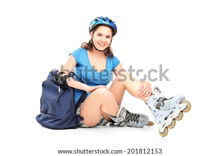 Schoolgirl with roller skates sitting on the ground isolated on white background - stock photo