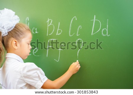 Schoolgirl writes English alphabet with chalk on a blackboard in school classroom. She does not know continuation of the alphabet and wrote a question mark. - stock photo