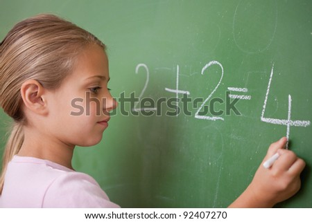 Schoolgirl writing a number on a blackboard - stock photo