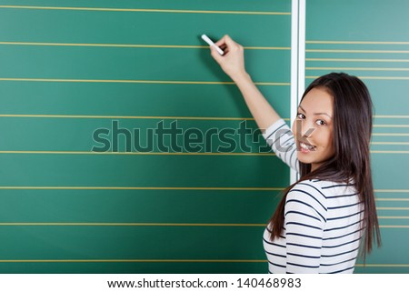 schoolgirl writing on blackboard in class room - stock photo