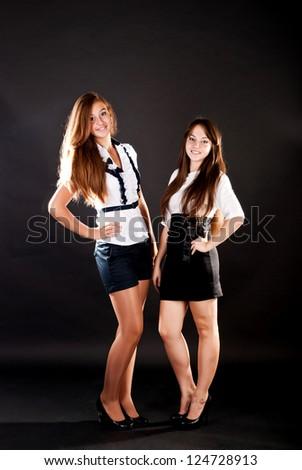 schoolgirls on a black background in a studio - stock photo