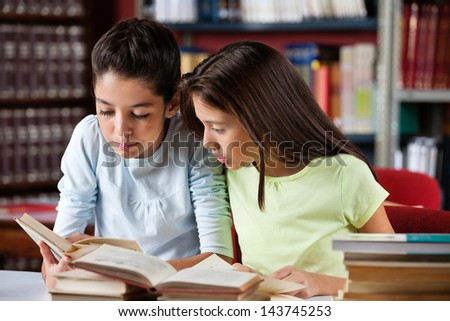 Schoolgirls reading book together while sitting at table in library - stock photo