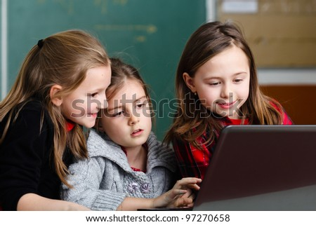 Schoolgirls working with laptop in classroom - stock photo