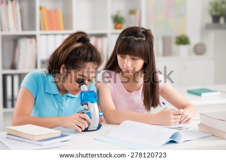Schoolgirls working with microscope during biology lesson - stock photo