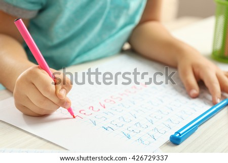 Schoolkid learns to write on sheet of paper, closeup - stock photo