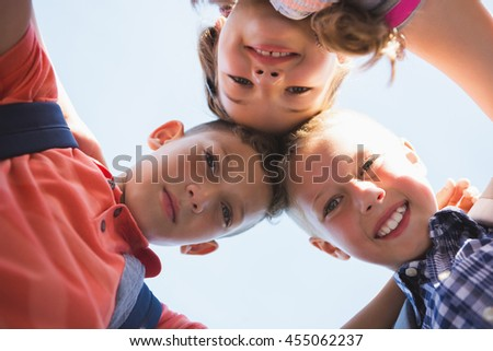 Schoolkids forming huddle in campus at school - stock photo