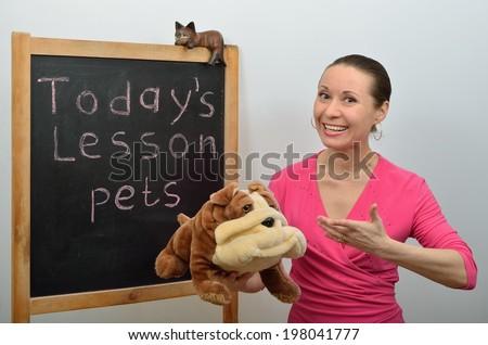 Schoolmarm woman tells children about pets - stock photo