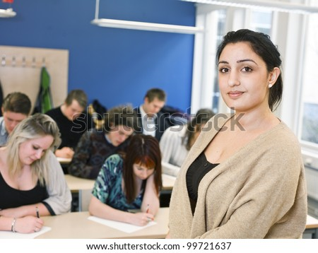 Schoolteacher in front of pupils in the classroom - stock photo