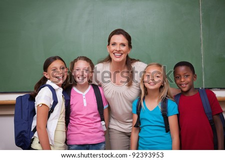 Schoolteacher posing with her pupils in a classroom - stock photo