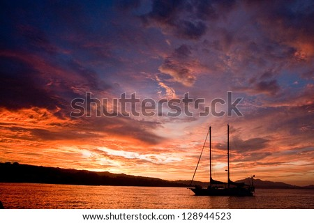 Schooner at anchor on Guadalcanal Island in Solomon Islands in South Pacific at sunset - stock photo