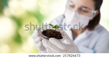 science, biology, ecology, research and people concept - close up of young female scientist wearing protective mask holding petri dish with plant and soil sample over green background - stock photo