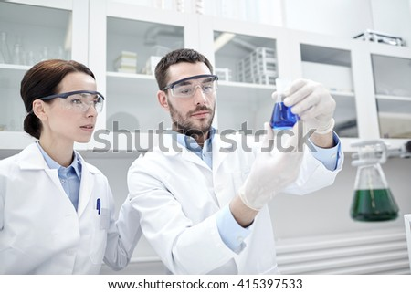 science, chemistry, technology, biology and people concept - young scientists with glass flask or test tube making research in clinical laboratory - stock photo