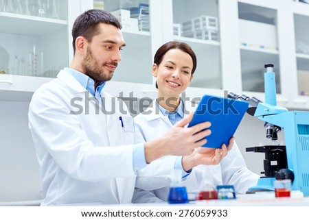 science, chemistry, technology, biology and people concept - young scientists with tablet pc and microscope making test or research in clinical laboratory - stock photo