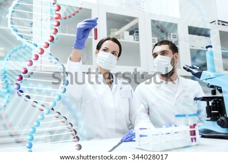 science, chemistry, technology, biology and people concept - young scientists with test tube and microscope making research in clinical laboratory over dna molecule structure - stock photo